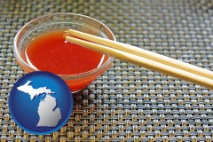 michigan map icon and chopsticks and red hot sauce in a Chinese restaurant
