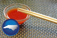 north-carolina map icon and chopsticks and red hot sauce in a Chinese restaurant