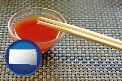 south-dakota map icon and chopsticks and red hot sauce in a Chinese restaurant