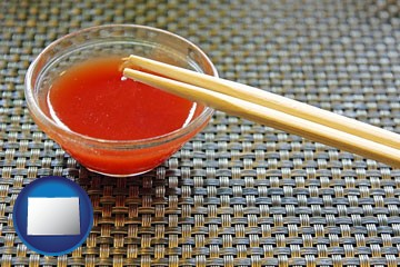 chopsticks and red hot sauce in a Chinese restaurant - with Colorado icon