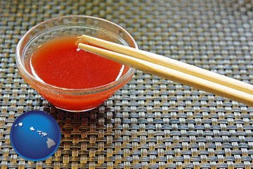 chopsticks and red hot sauce in a Chinese restaurant - with Hawaii icon
