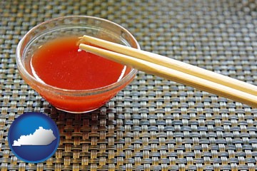 chopsticks and red hot sauce in a Chinese restaurant - with Kentucky icon
