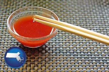chopsticks and red hot sauce in a Chinese restaurant - with Massachusetts icon