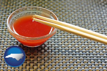 chopsticks and red hot sauce in a Chinese restaurant - with North Carolina icon